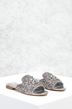 7677ac39a06d4d A pair of glitter textured loafer slides featuring a rhinestoned design