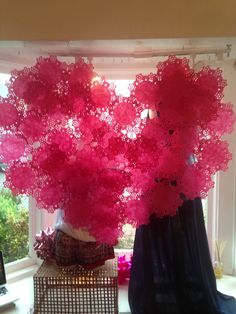 We just made this window display, stapling together pink doilies. It cost less than $10. Hurray for Valentine's Day!