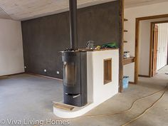 cool idea for a fireplace so you warm up the thermal mass wall behind it.... cob walls inside with clay renders, lime rendered external strawbale walls...