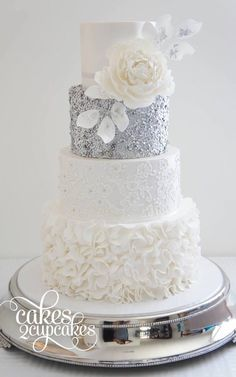 Silver and white wedding cake with flower accent | Sequin Wedding Cakes with metallic gold and silver accents via @Belle The Magazine #weddingcakes