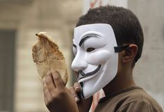 An Egyptian boy wearing a Guy Fawkes Mask holds bread, a symbol of poverty, during an anti-Muslim Brotherhood demonstration in Cairo, Egypt, on March 22, 2013. Thousands of protesters from different areas of Cairo marched on Friday to express their rejection of the Muslim Brotherhood and President Mohammed Morsi's rule. (Photo by Amr Nabil/AP Photo /The Atlantic)