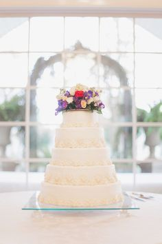 Simple #white wedding #cake with rustic purple flower topper (Photo by Green Tree Photo)