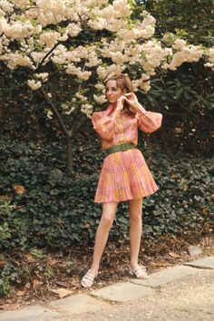 A model poses in a pleated, paisley-patterned pink skirt & matching blouse and a green belt as she poses next to a garden path in Dumbarton Oaks Park, Washington DC, May 1970.