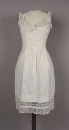 1875 Chemise Culture: American Medium: cotton, lace Chemise; white cotton, sleeveless with crocheted lace around neckline and armholes. Wide scoop neck. Crocheted lace straps. Center front button closure with seven white buttons. Fitted bodice with darts. Center back panel is gathered at lower back. Hem is accented with horizontal pintucks and crocheted lace.
