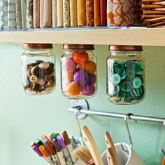 LOVE unique storage ideas! This would be so easy! Just screw the jar lids to the shelf and you have a way to display bright small buttons and items! Also love the idea of hanging cups for things like brushes and pens.