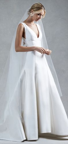 White sleeveless v neck silk mikado trumpet gown with satin bow detail