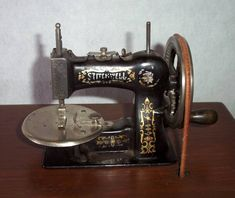 The National Sewing Machine Company made the Stitchwell cast iron toy sewing machines. This is a treadle model with two small drawers in the table.