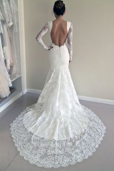 Lace wedding dress in a fit and flared trumpet silhouette with see-through lace panels in sides and an open back The wedding gown has a…