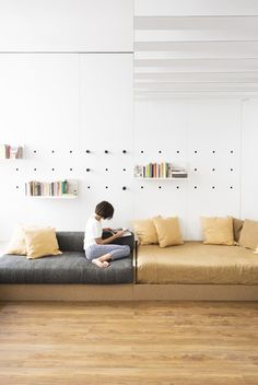 Living Room, Bench, Sofa, Medium Hardwood Floor, and Shelves Pegs slot into holes in the white laminate wall to support shelf units. Photo 7 of 8 in A Tiny Florence Flat Is Reborn as an Architect's Live/Work Space