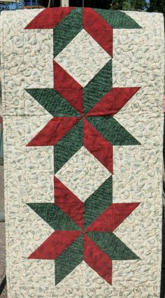 This beautiful table runner features three stars of green and red fabric surrounded by beige with green trees and gold and green ribbons.