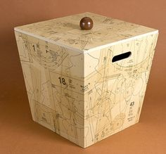Cover a wood box with pattern pieces and Mod Podge for a budget storage upgrade.