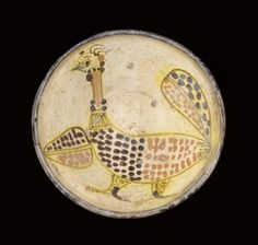 A POTTERY BOWL WITH PEACOCK, EASTERN IRANIAN WORLD, 10TH CENTURY  Of deep form, earthenware with white slip, decoration in black, red and yellow staining black slips under a transparent glaze, with large peacock with spotted wings, body to interior, abstract splashes of red and black to outer rim - 7in (17.7cm) diameter