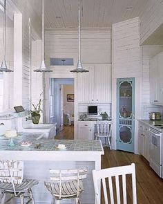 The creative use of a screen door for the pantry makes this beachy kitchen extra awesome