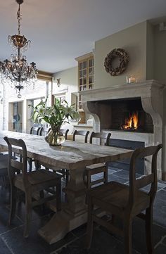 Achterhuis:  dining room with crystal chandelier over salvaged wood trestle dining table ...