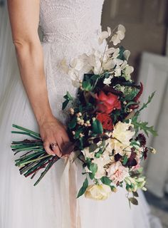 moody bridal bouquet with red, yellow, white and green blooms.