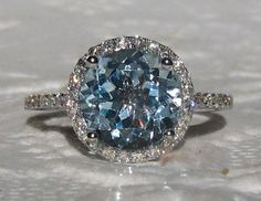 A beautiful and delicate engagement ring featuring a sparkly aquamarine in white gold diamond halo. The center stone is a round aquamarine,