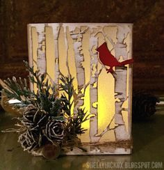 "Luminaria by Stamptramp. Supplies: Tim Holtz tattered pinecone, birch trees, mini cardinal and poinsettia, holiday greens, and ""frosted film"" (vellum?) Pumice stone and antique linen distress ink. Picket fence paint."