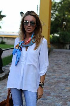 A colorful silk scarf worn with a white oversized blouse and jeans for a casual chic look.