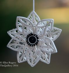 This quilled paper white anemone flower Christmas ornament is handmade from white and black strips of paper. Its made by hand and then sealed with clear sealer and a string is attached along with a metal ornament hook. You will be able to hang it right out of the box! This would look