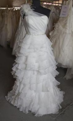 Jasmine T496//Size 6 - Lux Organza bridal gown with a unique one shoulder neckline, a flattering pleated bodice, a slimming flower waistband, as well as a striking ruffle skirt that is also detachable!