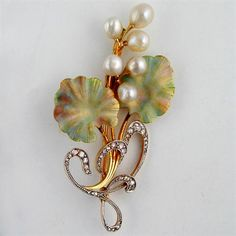 An Art Nouveau enamel, pearl and diamond brooch, the sinuous curling spray with six graduated pearl berries and opalescent shaded enamel lea...