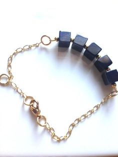 This unique bracelet is so chic, and it is such a conversation piece. It has deep bluish-gray cubes with small round gold beads in between and can be made to a custom size. #scottsmarketplace