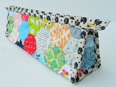 "I used Ayumi's tutorial, just like Leila did, but I made a few adjustments to my pouch's size since I did not want to waste any of the hexies. The pouch I made is a little bit longer (about 10"" long) which turned out to be a perfect size to fit my most used sewing supplies."