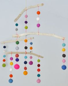 Móvil realizado con bolas de fieltro ideal para un escaparate infantil. Pineado por Pilar Escolano