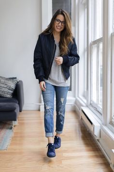 Blue bomber jacket with a grey tee and distressed jeans