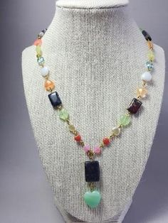 This precious necklace is made with different colors Czech glass beads in a heart shape, gold metallic beads and square green stone in the center. The necklace is measure approximately 18 inches. Ther