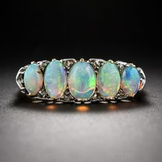 English Antique Opal and Diamond Ring, A quaint quintet of opals, dotted in between with tiny rose-cut diamonds, harmonize in glowing pastel colors in this classic Victorian 'carved' ring by way of Chester, England - circa 1912 (the array of hallmarks inside the ring shank tell all). Hand fabricated in 18K yellow gold with silver diamond settings and fleur-dy-lys adorning the shoulders