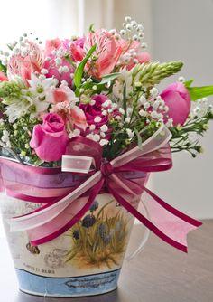 Arreglo floral con maceta de lámina cuadrada con asas de metal, estampado azul, beige y flores Medida aproximada: 12x12x18 cm Ideal para obsequiar el día de las