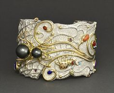 Sterling silver tufa cast cuff bracelet with 18K gold set with Tahitian and white pearls, coral, lapis, sugilite, and white and colored diamonds by Jesse Monongye (Navajo)