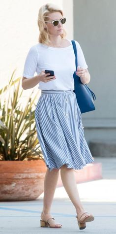 January Jones gave her off-duty style an easy, breezy spin by styling a white tee with a summery striped button-front skirt, a navy tote, and nude stacked sandals.
