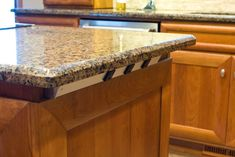Angle power strip under counter top overhang on kitchen island