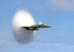 Above, an F/A-18 Hornet breaks the sound barrier; the shock wave causes a drop in pressure. As a result water droplets condense and sometimes forms a cloud, as seen above.    (Photo via Wikimedia Commons)