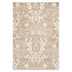 Bring classic style to your master suite or home office with this hand-tufted wool rug, showcasing a floral motif in beige and cream.