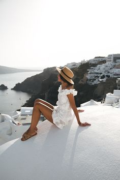 SANTORINI POSTCARDS - Lovely Pepa by Alexandra. White off the shoulder floral embroidery ruffle romper+camel flat sandals+hat. Summer Vacation Outfit 2017