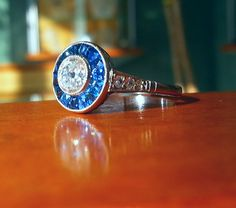 Vintage engagement ring with halo of sapphires