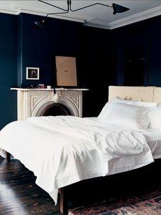 More dark blue walls with dark wood flooring.