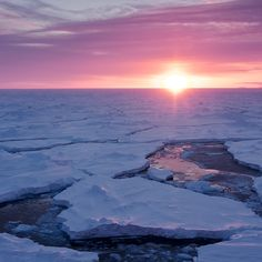 The sun setting over a field of broken sea ice, or frozen seawater that floats on the ocean, in Antarctica.