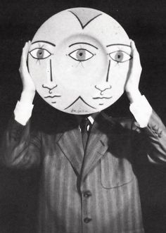 Jean Cocteau holding a mask in front of his face