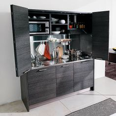 Small Kitchen Designs Ideas This Italian hideaway kitchen from John Strand is just over 1.7 metre wide but offers a larger preparation area and ample storage which can be discretely hidden behind the sleek bi-fold doors. more info : http://bit.ly/1ofiLNw