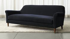 Sumptuous deep blue velvet and spare sweeping lines update the classic roll arm sofa with fresh simplicity and modern luxury. Bringing remarkable comfort to formal living rooms, the sofa has rounded arms that flare from the traditional, framing a streamlined yet plush bench seat.