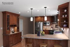 Kitchen remodel by Renovisions. Induction cooktop, stainless steel appliances, cherry cabinets, shaker cabinets, under cabinet lights, tuscan-clay-look porcelain tile backsplash, quartz countertop, office station, organizational station, peninsula, hardwood flooring, pendant lights, recessed lights, corner stove.