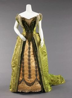 """1887 -This is truly an attention getting evening gown with """"fantasy"""" theme depicted in the bodice which imitates a peasant's cotton blouse and is played against the traditional 18th century and neoclassical motifs in the skirt embroidery.  Designed by Charles Worth."""