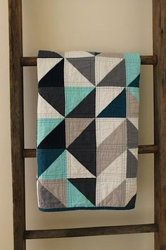 ladder repurposed as quilt storage rack - this would totally be a better way to 'store' gently worn sweaters or jeans for the next day :)