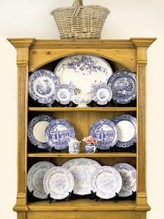 All Symmetrical Here, an arrangement of blue-and-white plates and platters gains interest from a range of blue tones and a variety of sizes, framed in a vintage-look pine cupboard Blue Plates, Decor, Dish Display, Plate Display, Blue And White, Plates On Wall, Wall Mounted Display Cabinets, China Display, White Decor