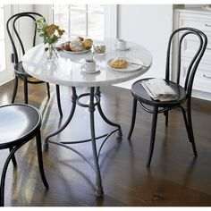 Shop French Kitchen Round Bistro Table.   Prized for its natural grey-white veining, the one-of-a-kind Carrara marble top is perfectly matched by its cast steel and aluminum base.