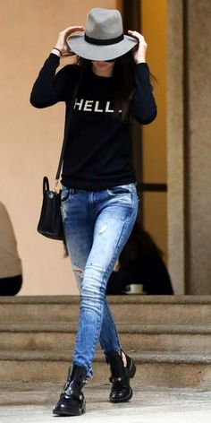 Kendall Jenner wearing a wide-brim hat, printed sweatshirt, skinny ripped jeans, and black Balenciaga ankle boots
